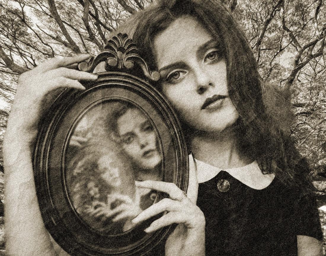 Eine gothic Frau mit einem Spiegel und ihrem Spiegelbild